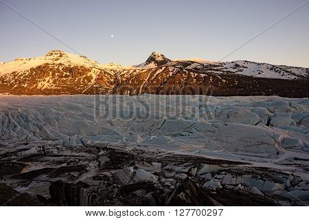 Offshoots of a glaciers tongue in front of mountains in iceland with moon