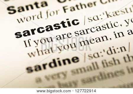 Close Up Of Old English Dictionary Page With Word Sarcastic.