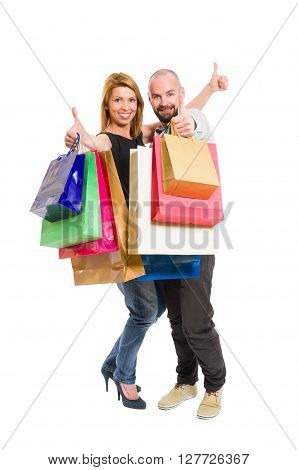 Happy shopping couple showing thumbs up standing isolated on white backrgound