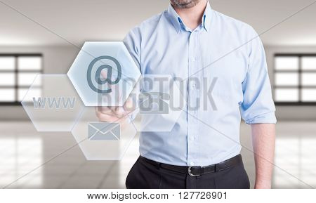 Contact us using email concept with man pressing button on transparent futuristic touch screen