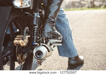 Back view of senior couple legs with boots sitting over motorcycle ready to go