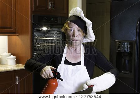 Mature woman standing in a kitchen with singed face holding pan and fire extinguisher with chefs hat and apron.