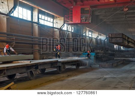 Tyumen, Russia - August 13, 2013: Finished goods warehouse at Concrete Goods Plant No. 5. Worker prepares railway platform for transportation of factory production