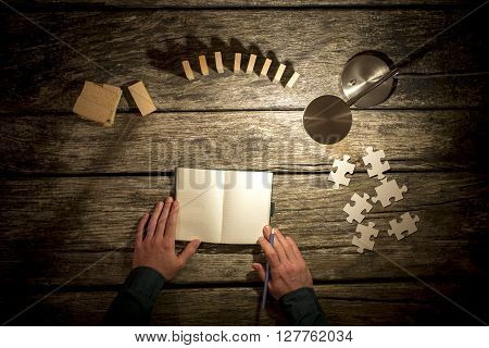 Top view of male hands about to make notes in blank notebook and various pegs dominos and puzzle pieces placed around it on wooden study desk with table lamp turned on.