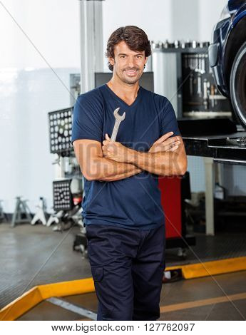 Smiling Mechanic Standing Arms Crossed At Garage