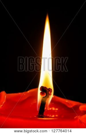 close-up of a tall flame on a red candle