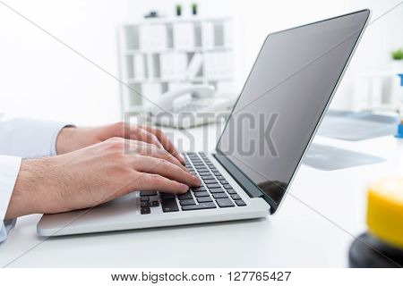 Sideview of doctor's desktop with hands typing on laptop with blank screen. Mock up
