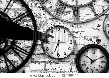 a hand points at clock hands on a wall