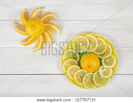 Flat lay of citrus fruit slices laid out on a saucer. Top view composition. Food decoration. Boosting immune system. Prevent kidney stones. Soothe a sore throat. Support weight loss. Bring down a fever.