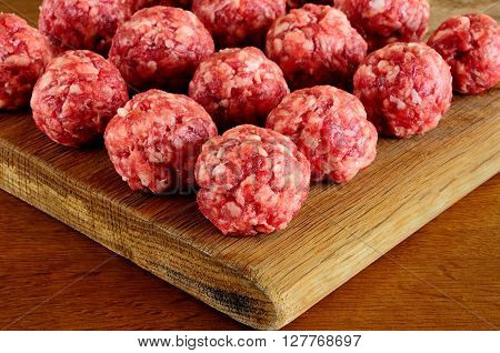 meat balls from raw beef force-meat on a chopping board