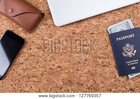 Topview of cork table with dollar banknotes inside american passport smartphone and eyeglass case. Traveling concept. Mock up