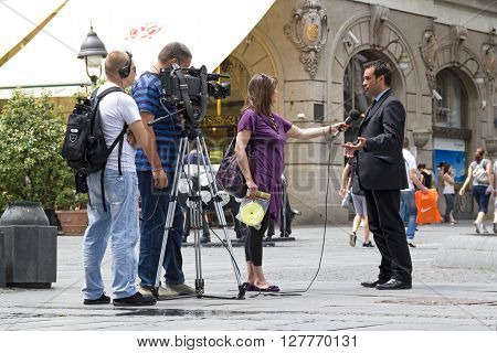 BELGRADE, SERBIA - JUN 9, 2011: RTS cameraman, sound recordist and TV reporter on the street holding an interview with a man in a suit