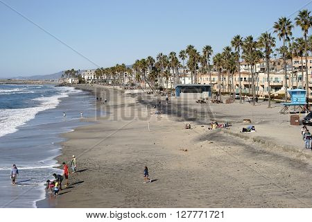 OCEANSIDE, UNITED STATES - DECEMBER 25, 2015: Visitors and tourists enjoying themselves in fine weather at the beach of Oceanside on December 25, 2015 in Oceanside.