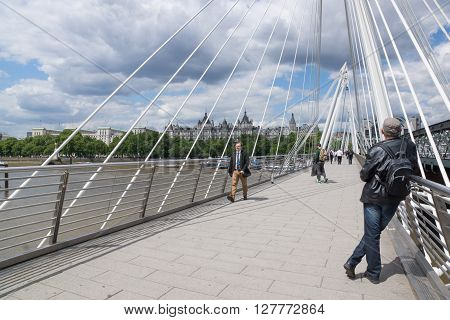 London, United Kingdom - June 8 2015: Pedestrians crossing the Thames River on the Golden Jubilee Bridge