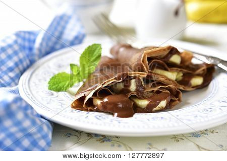 Chocolate Pancakes With Banana And Chocolate Sauce.