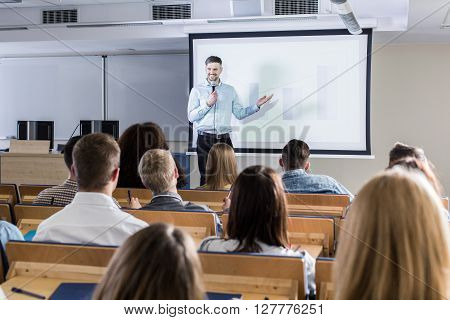 Image of a teacher giving a lecture to his students