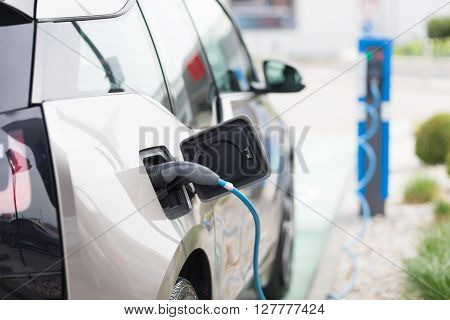 Power supply for electric car charging.  Electric car charging station. Close up of the power supply plugged into an electric car being charged. poster