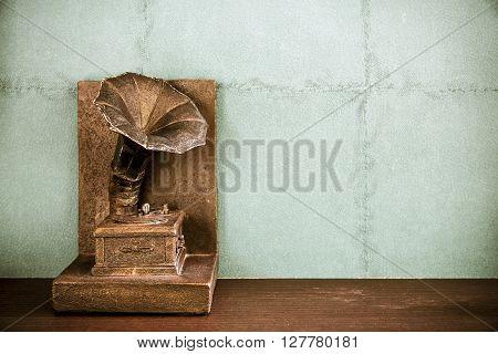 Vintage imitation turntable or gramophone on wall background.