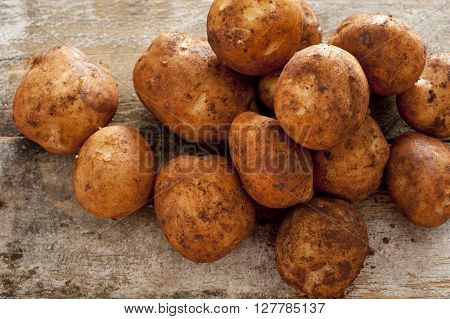 Farm fresh or home grown rustic potatoes covered in dirt in a heap on an old wooden kitchen table high angle close up view