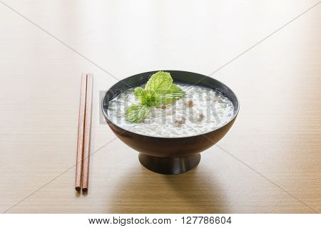 Traditional chinese rice gruel in bowl on wood table