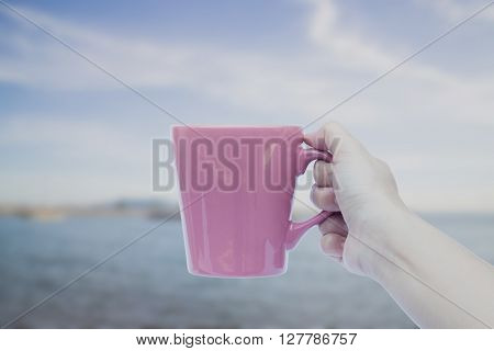 Woman hand holding coffee cup with blur deep blue background, stock photo