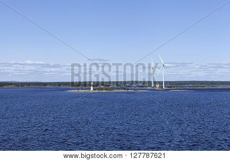 A lighthouse, beacon and windmills on the shore. Islands, buildings and mainland in the background. Sunny day.