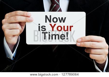 Now is Your Time. Businessman holding a card with a message text written on it