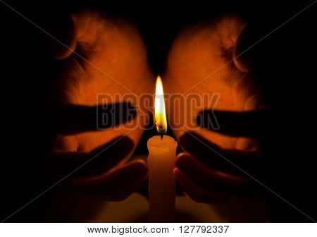 Spell And Spirituality Topic: Witches Hand Holding A Candle On A Dark Background