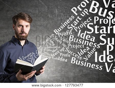 Education concept with businessman standing against concrete wall and holding a book with business related words flying out of it