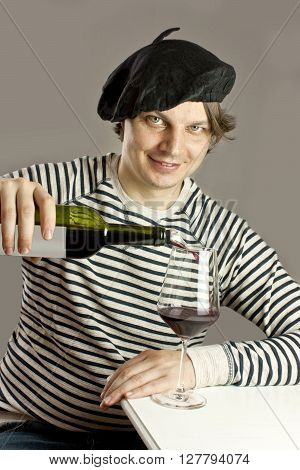 A photo of an attractive smiling Frenchman in traditional clothes (a beret and a striped sweater) pouring himself a glass of red wine from a bottle with an aerator sitting at a white table
