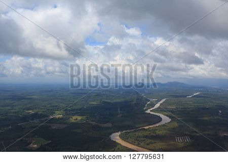 aerial top view from air plane see river and green hills field with clear white cumulus cloud and cloudscape on blue sky