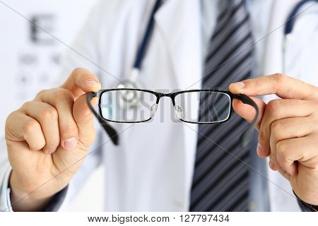 Male Medicine Doctor Hands Giving Pair Of Black Glasses