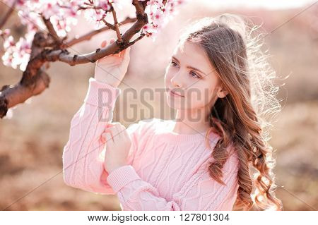 Beautiful blonde teenage girl 14-16 year old holding peach tree in garden. Posing outdoors. Wearing knitted sweater. Looking away.