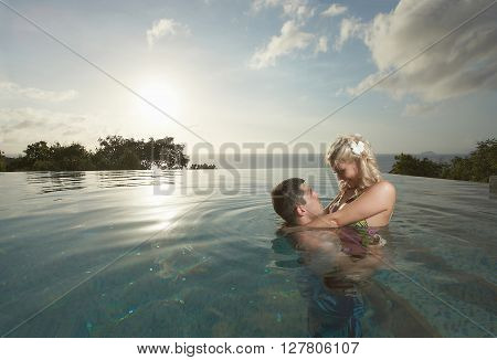 Young, Sexy And Attractive Couple Kissing In Swimming Pool In Sexual Embrace.