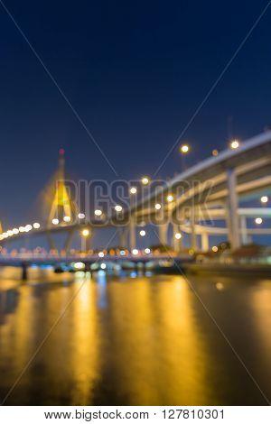 Blurred bokeh lights, suspension bridge and highway at twiligh