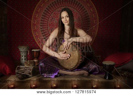 Young Caucasian woman playing drum ethnic musical instrument