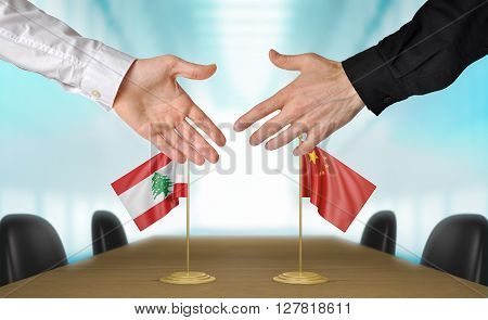 Lebanon and China diplomats shaking hands to agree deal