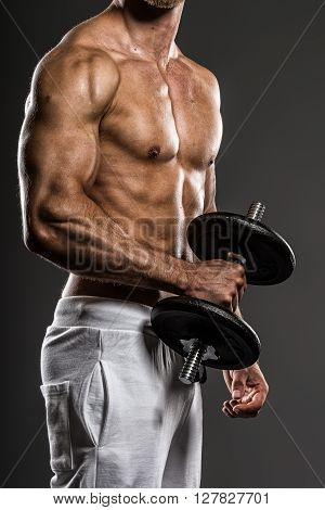 Muscle detail of handsome young bodybuilder training with dumbbells, on grey background