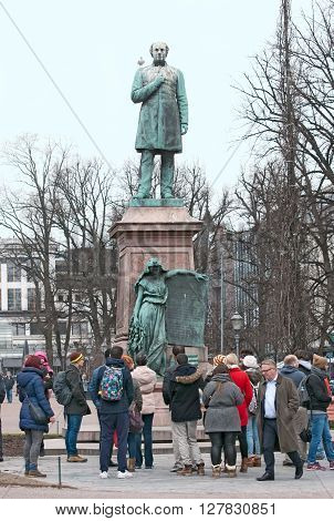 HELSINKI, FINLAND - APRIL 23, 2016: Tourist group near statue of Johan Ludvig Runeberg, national poet of Finland. Was built in 1885. Located in Esplanade Park in the center of Helsinki.