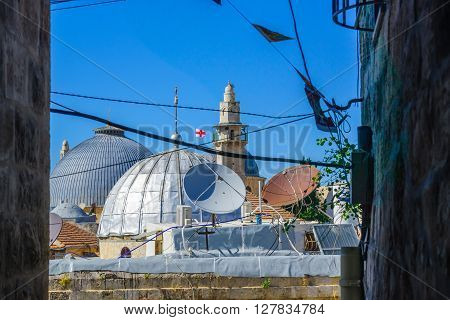 JERUSALEM, ISRAEL - APR 28, 2016: View of the roof of the church of the Holy Sepulcher and a minaret of a nearby mosque from an alley in the old city. Jerusalem Israel