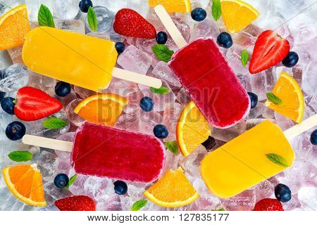 refreshing fruit popsicle lollies on ice background with berries and peppermint.