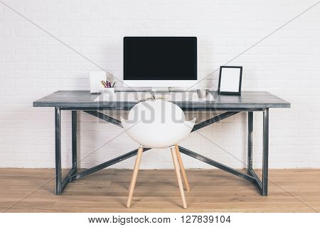 Front view of designer desk with blank computer monitor frames and other items with white chair next to it. Wooden floor and white brick wall background. Mock up. 3D rendering.