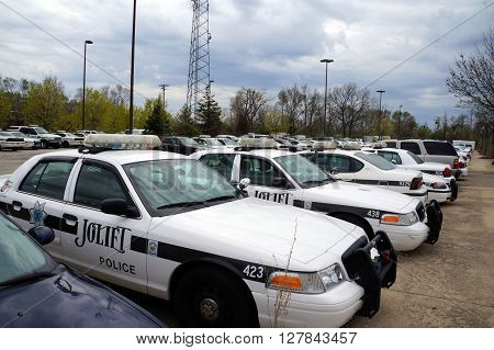 JOLIET, ILLINOIS / UNITED STATES - APRIL 19, 2015: Police cars are parked in the parking lot behind the police department in downtown Joliet.