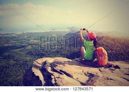 young woman hiker use smartphone taking photo on seaside mountain top
