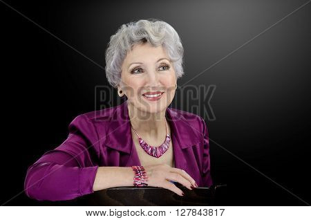 Facial shot of classy 76-year-old woman wearing pink fuchsia mother of pearl shell stick beads and bracelet. Grey haired senior woman dresses in magenta blouse and poses on black background