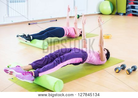 Fit women doing workout, yoga pilates back bend exercise at fitness club.