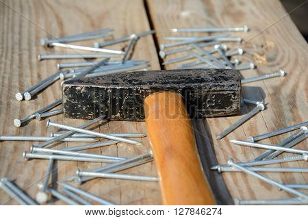 Hammer and batch of nails on wooden planks. Shallow depth of field.