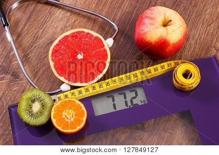 Digital electronic bathroom scale for weight of human body tape measure and medical stethoscope with fresh fruits concept of healthcare healthy lifestyles and slimming