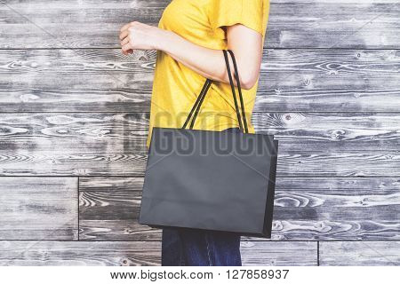 Sideview of girl with blank shopping bag on antique wooden background. Mock up