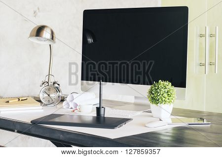 Sideview of designer desktop with black computer screen graphic tablet alarm clock and other items. Concrete wall and glass door in the background. Mock up